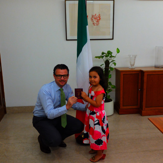 ambassador mclaughlin presents a new irish passport to a child