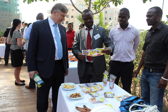 Stephen Isiko, a local business man, showing the Secretary General, David Cooney, what his company produces