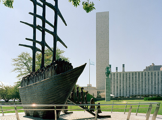 "The sculpture (measuring 26 x 24 ft) is made in bronze, entitled ""Arrival""  and is by Dublin-born sculptor John Behan.  It weights more than 11 tons, and depicts emigrants disembarking from the ship along two gangplanks towards New York's East River. It was presented by the Irish Government to the UN in 2000."
